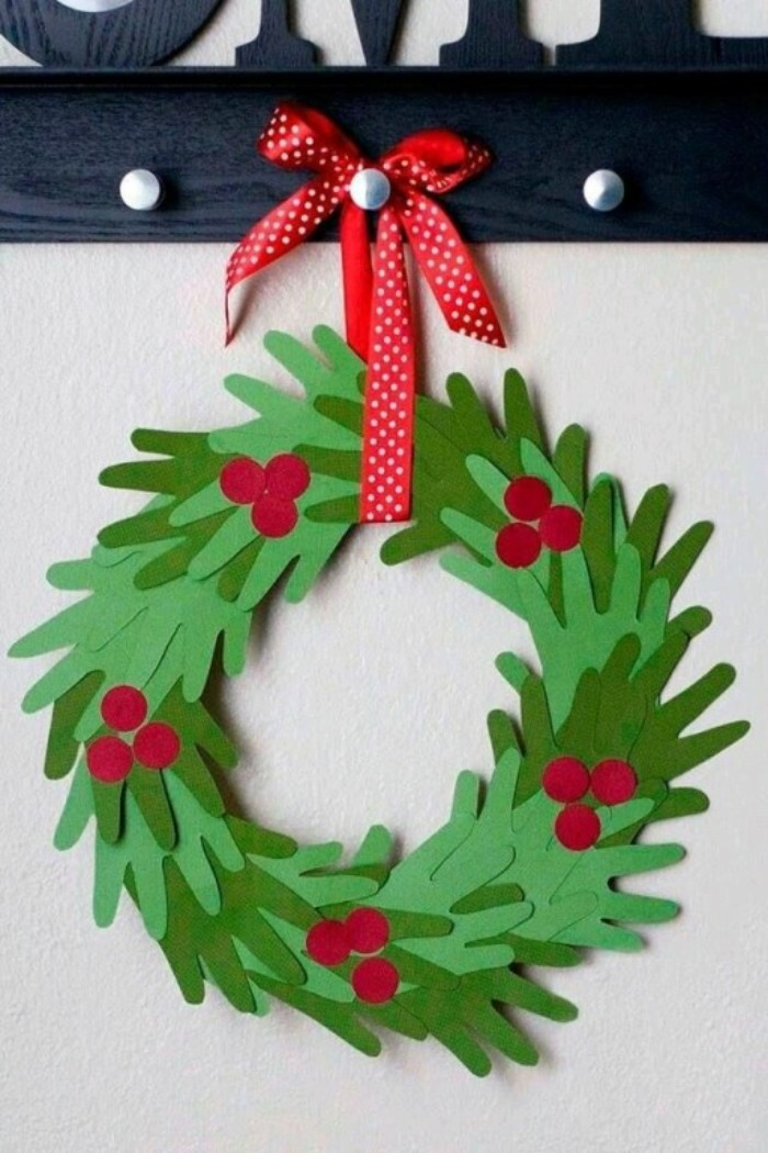 cutouts shaped like a child's hand, made from light green, and dark paper, and decorated with round red shapes, stuck together to form a wreath, decorated with a red and white ribbon, how to make a christmas wreath