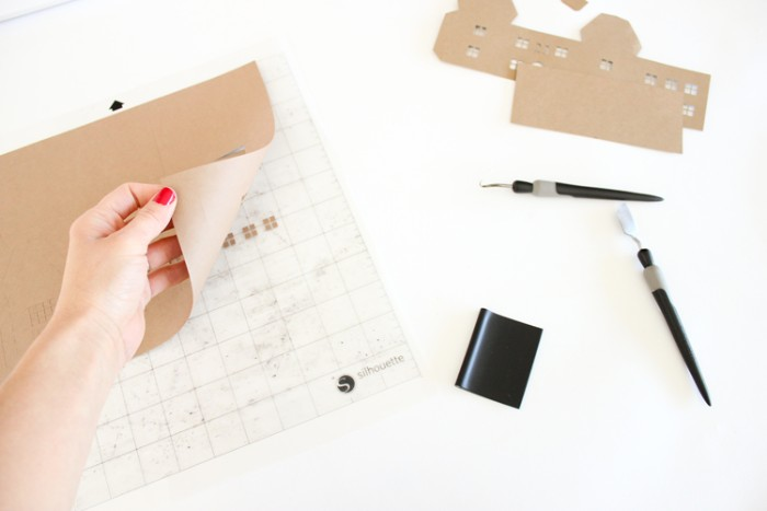 nail polish in red, on a hand, pulling a piece of beige card, away from a sheet of white, see through lined paper, adult advent calendar making process, two pen knives, and some cutouts nearby
