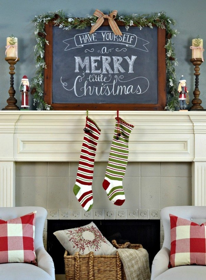 pair of striped stockings in white, red and green, hanging from a white mantelpiece, near a blackboard with the message, have yourself a merry little christmas, written in white chalk, mantel decor
