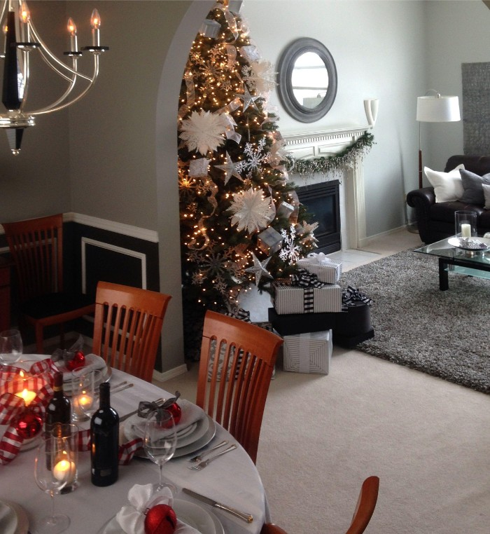 table set for a festive dinner, in a dining area, overlooking a living room, decorated with a christmas tree, covered in white ornaments, and glowing string lights, holiday images, presents and a festive garland