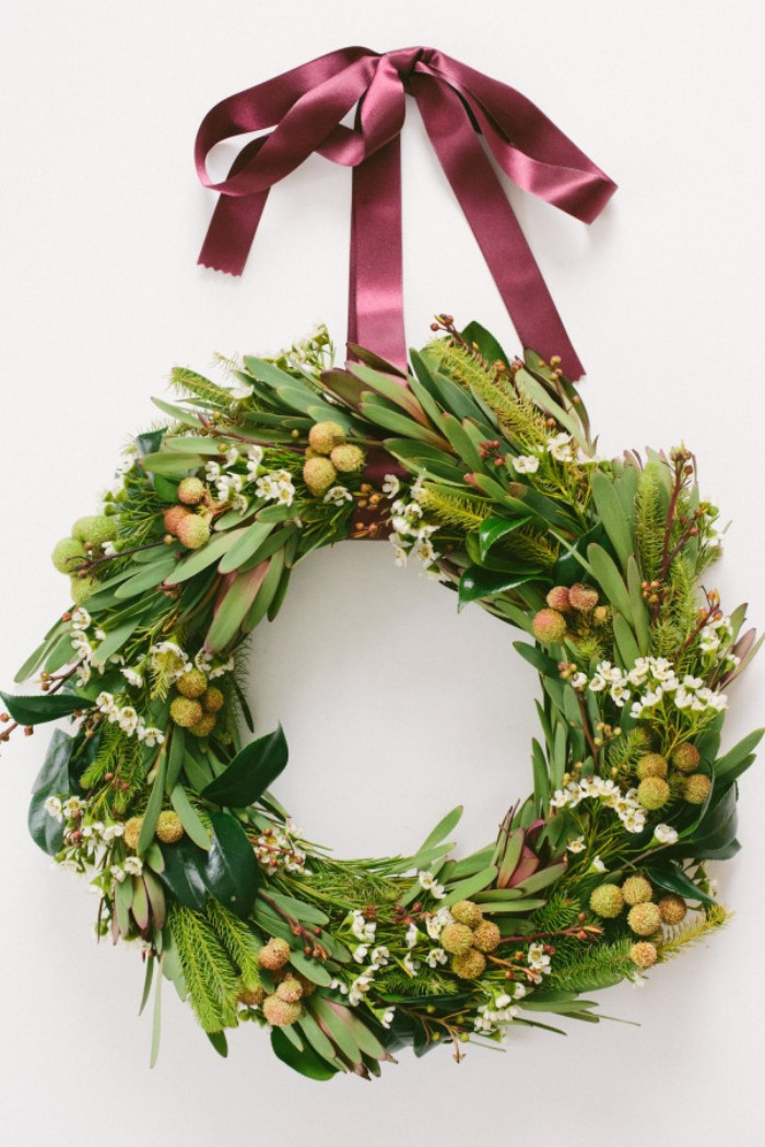 mistletoe leaf wreath, decorated with small white blossoms, and mistletoe berries, with a silky maroon ribbon, attached to a white wall, christmas wreath images