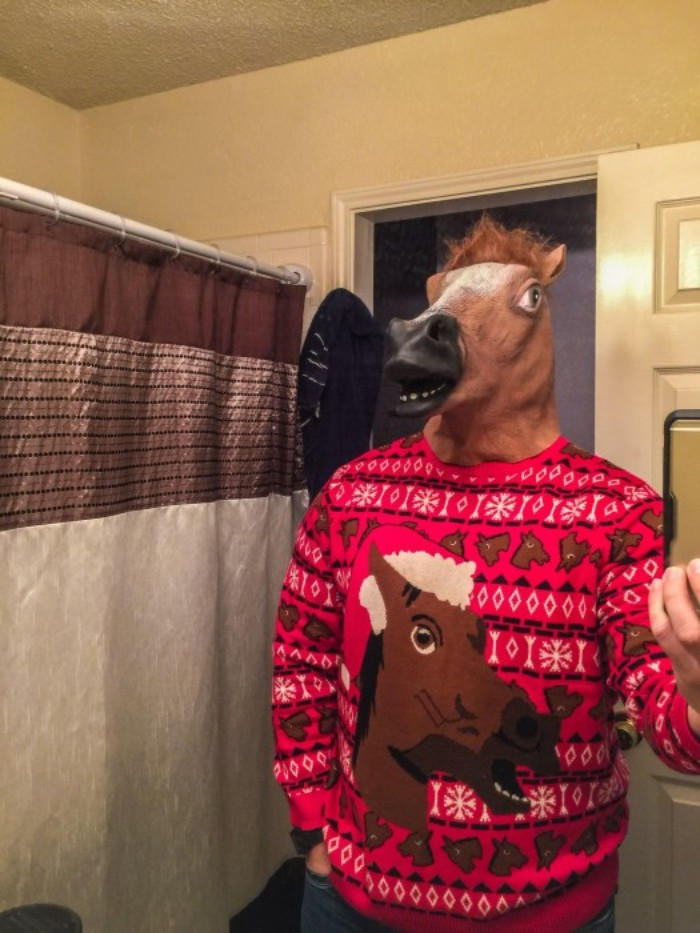 guy in a brown, plastic horse mask, dressed in a red jumper, with a large, brown horse head image, and a pattern, with smaller horse heads, and white snowflakes