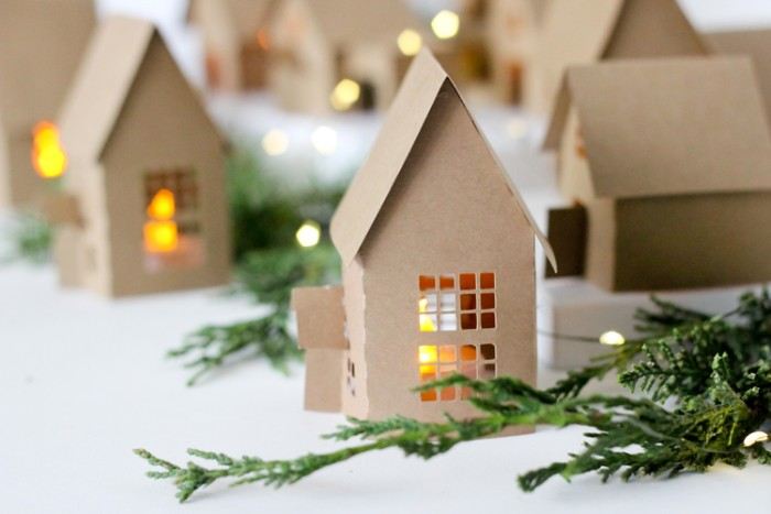 adult advent calendar tutorial, small cardboard houses, with cutout windows and doors, each containing a lit tea light, forming a christmas village, surrounded by pine branches