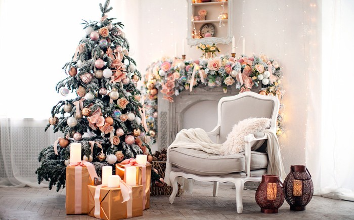 peach pink roses and baubles, decorating a white mantelpiece, and a christmas tree, inside a bright living room, christmas mantel ideas, presents and candles nearby