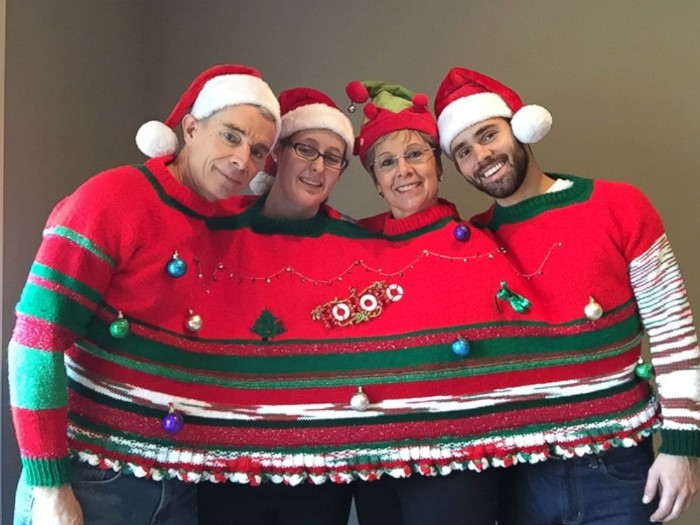 shared family jumper, in red and green, decorated with baubles and ornaments, worn by a family of four, with santa hats, cute ugly christmas sweater