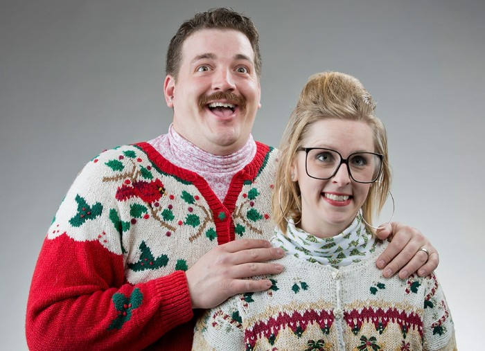 cardigan in red and white, with green holly branches, and a robin, worn by a smiling man, with a mustache, and a pale pink turtleneck, hugging a blonde woman,in a similar kitsch retro cardigan