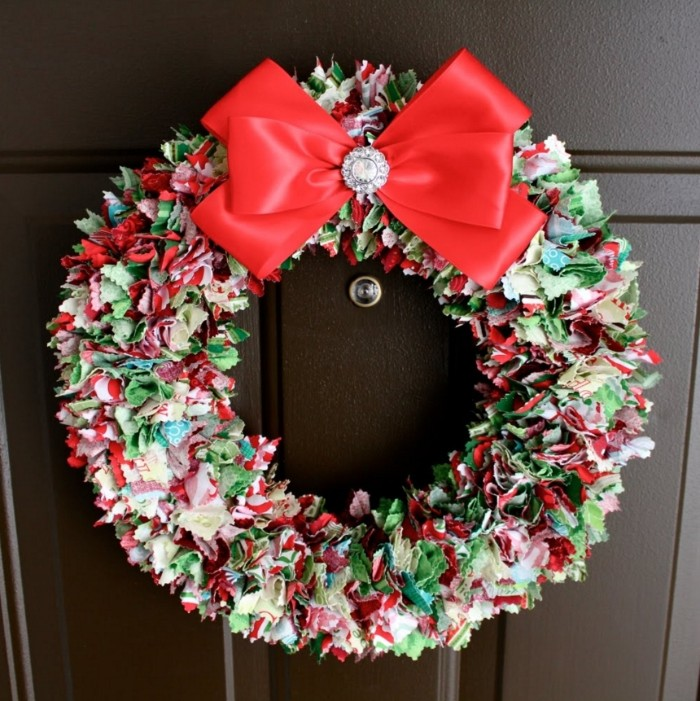 ribbons in various colors, tied together on a round frame, to create a christmas wreath, decorated with a large red bow, featuring a silver button, wreath ideas, on a dark brown door