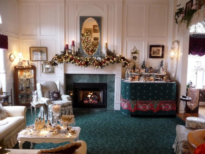 spacious living room, with fireplace mantel decor, featuring a garland, covered in glowing fairy lights