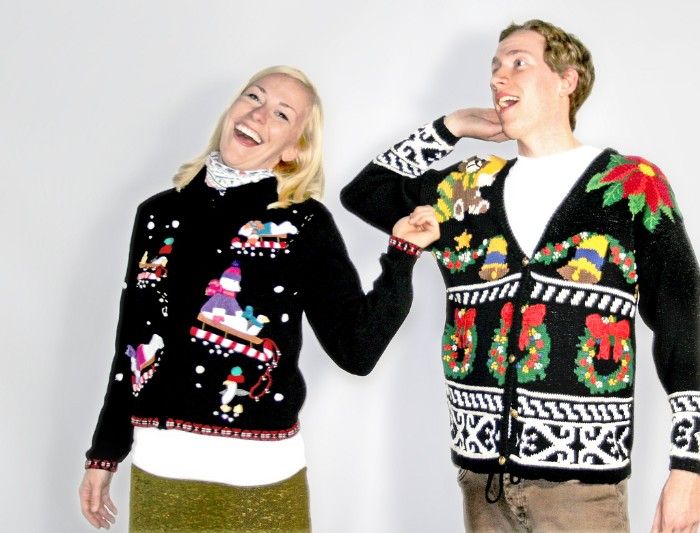 straw blonde woman, laughing and wearing a black festive jumper, with colorful sleds and snowmen, near a laughing man, in a black cardigan, decorated with bells and christmas wreaths