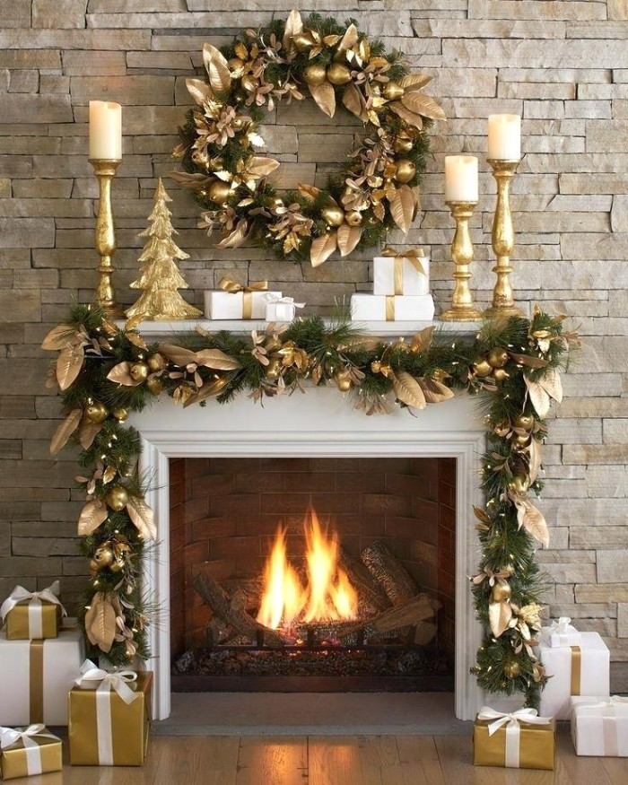 gold leaves decorating a green wreath, made from faux pine leaves, and a similar green garland, draped over the mantelpiece of a burning fireplace, christmas mantel ideas, in green and gold
