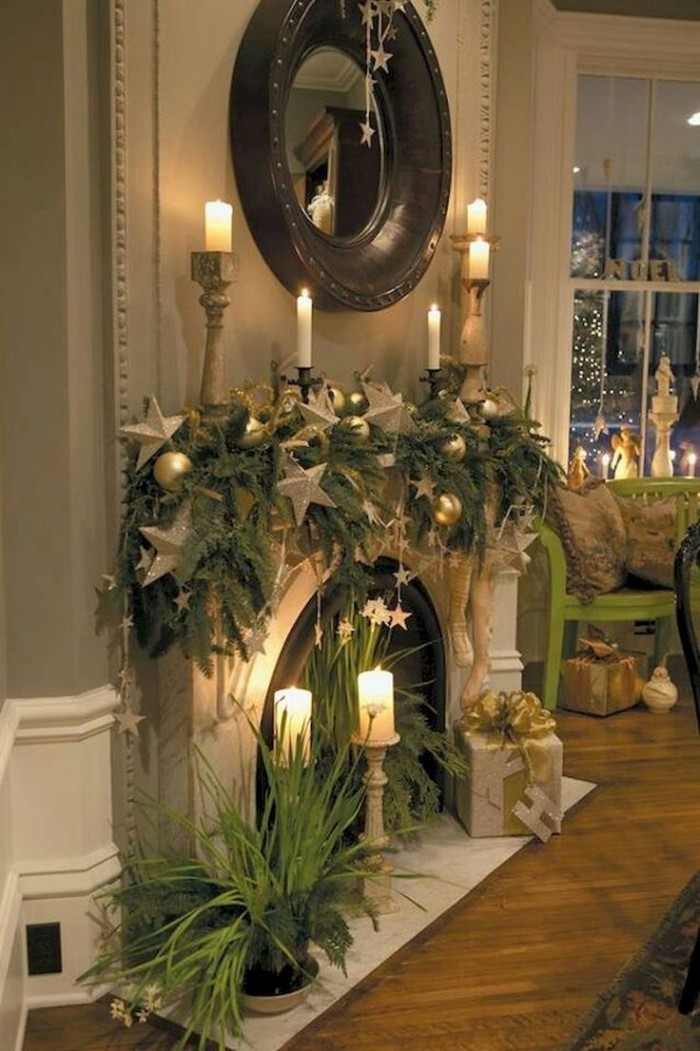 laminate flooring near a fireplace, decorated with pine garlands, silver star-shaped ornaments, and burning candles