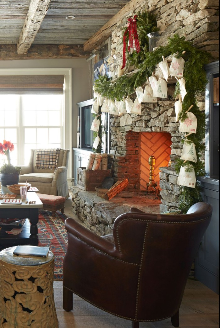 fireplace made of stone, decorated with fir branches, and an advent calendar, featuring cream paper bags, in a country chic living room