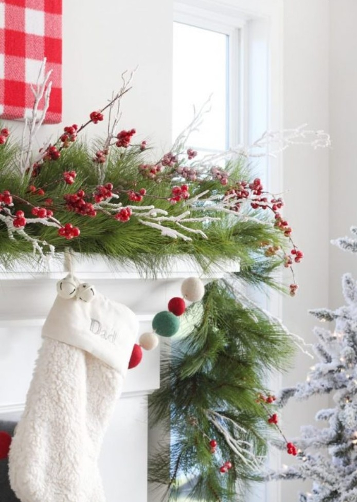 tiny red faux berries, on thin white branches, decorating a garland, made from longleaf pine branches, placed on top of a white mantelpiece, with a single white stocking