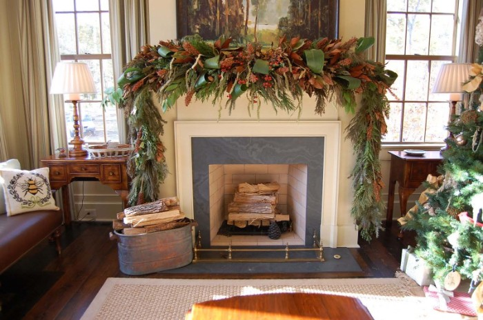 19th century style room, with a fireplace, displaying a lavish mantel decor, featuring a voluminous green garland, made of various branches and leaves