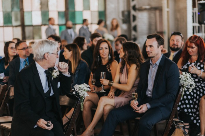 guests at a wedding, or another formal event, sitting on chairs, some with champagne flutes in their hands, dressed in black tie optional attire, black and dark navy suits, with white and light colored shirts, smart occassion dresses