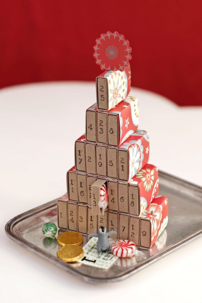 diy advent calendar, made from several matchboxes, decorated with colorful patterned paper, and stacked to form a christmas tree, various candies and a small toy
