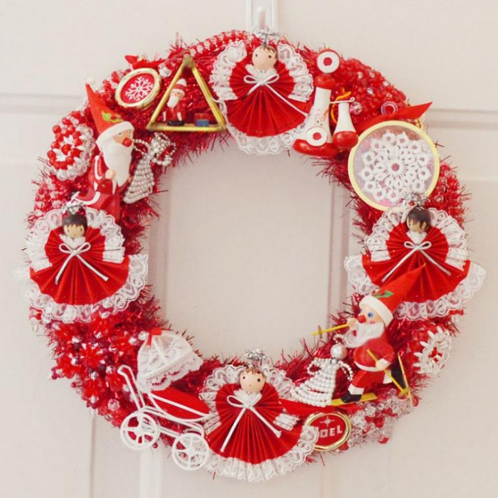 dolls and small decorations, in red and white, on a diy wreath, made from a red fuzzy garland, and hung on a white door