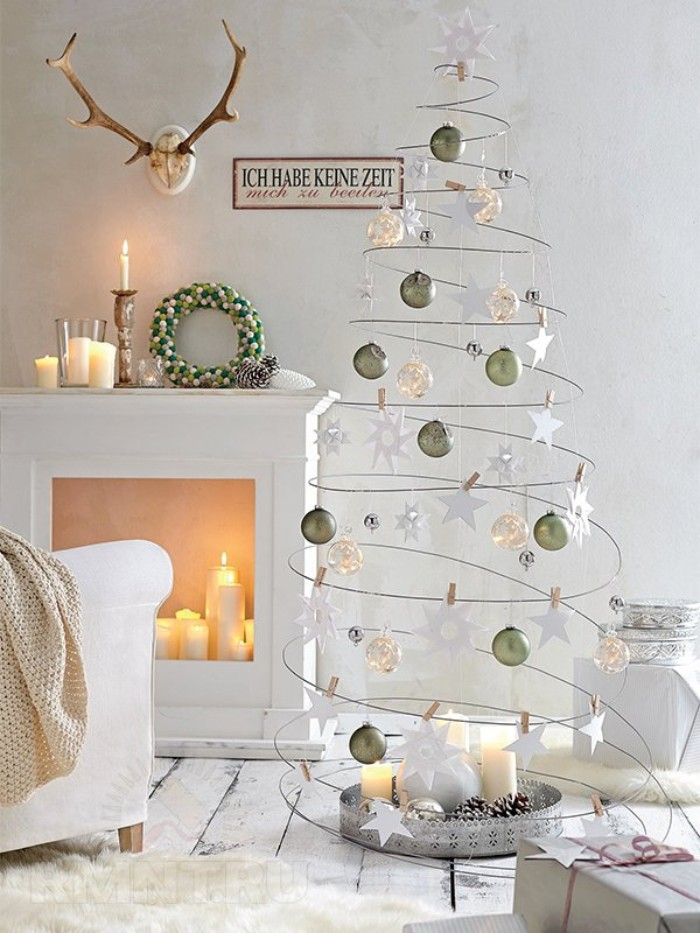 xmas tree made from wire, twisted into an upward spiral, and decorated with white, silver and gold baubles, small wreath and several candles, on a diy fireplace mantel nearby