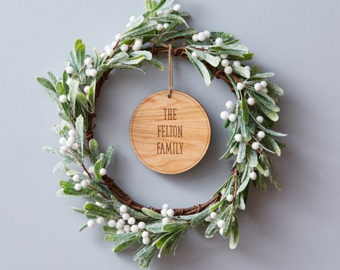 the felton family, etched on a round wooden tag, attached to wreath, made from mistletoe branches, christmas wreath images, green leaves and white berries, dusted with fake snow
