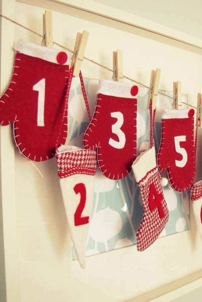 three decorative mittens, made from red and white felt, with a different white number on each one, advent calendar ideas, hat and stockings, all attached to a string line, with wooden clothes pegs