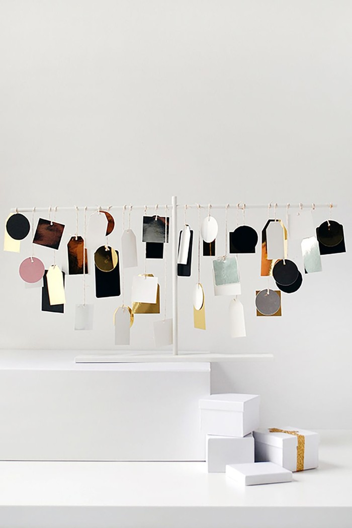 many labels in different colors, shapes and sizes, hanging on a white metal frame, minimalistic and modern advent calendar suggestion