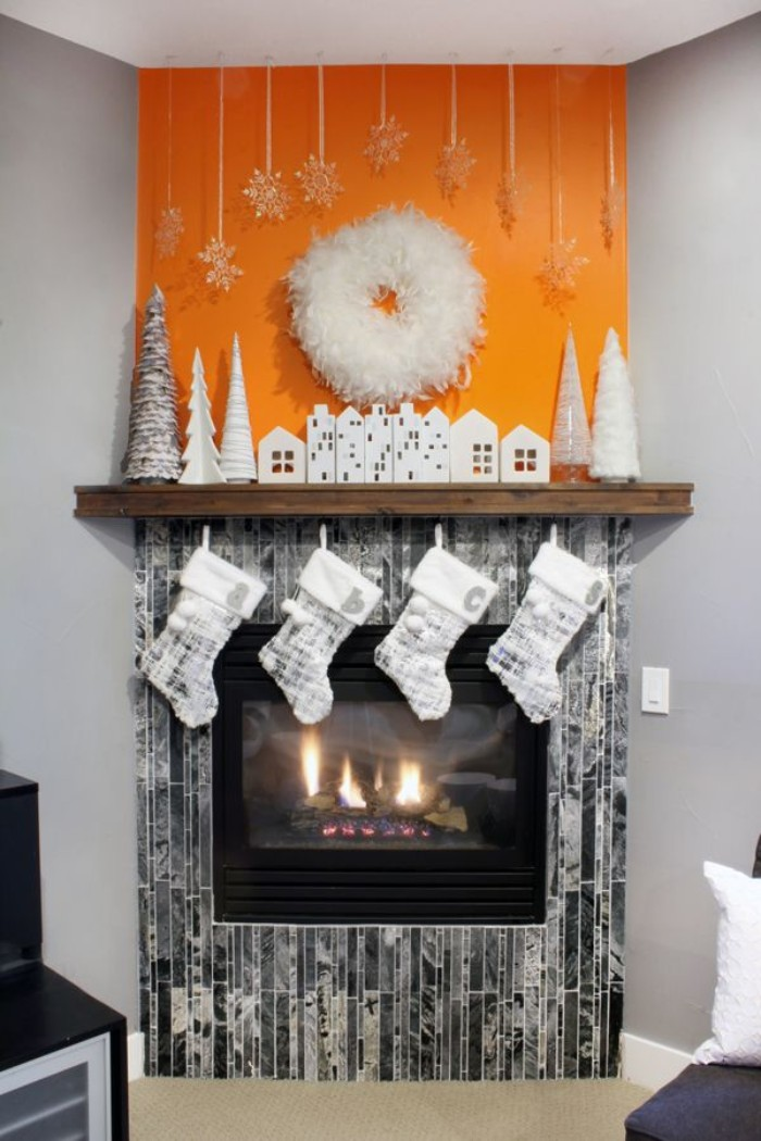 orange and grey walls, in a room with white, and silver chirstmas decor, featuring small house and xmas tree figurines, and four stockings, on a diy fireplace mantel