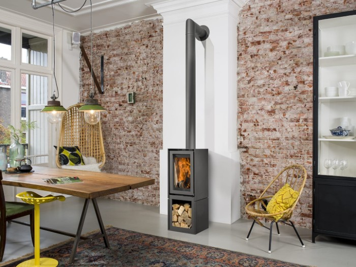 7 tips to make your home cosy, modern metal fireplace in black, with a firewood compartment, in a room with a brick wall, smooth light grey floor, wooden table and a black cupboard, rattan swing and chair