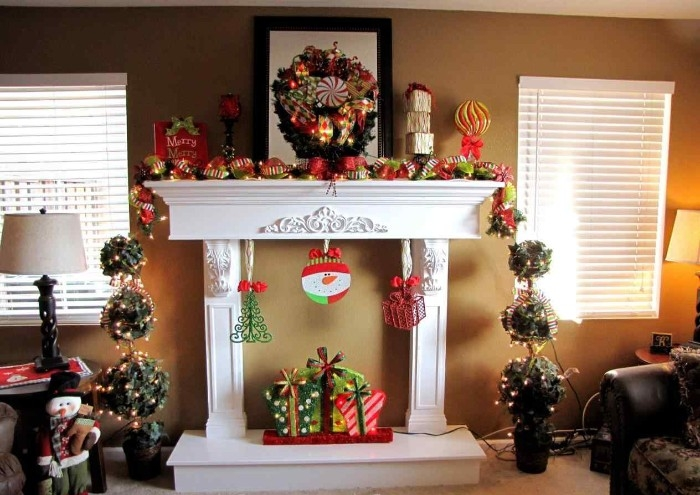 plaster ornaments on a white mantelpiece, without a fireplace, decorated with christmas garlands, presents and small xmas tree figurines, snowmen and others, images of christmas