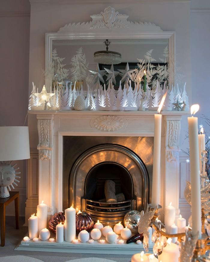 lots of burning white candles, in different shapes and sizes, near a vintage-style fireplace, in white and silver, decorated with multiple white, illuminated christmas tree figurines, christmas fireplace