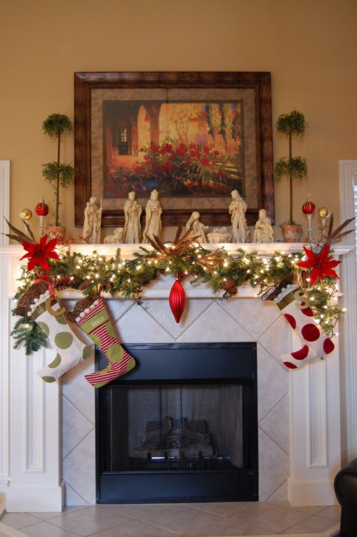 poinsettia flowers and a red ornament, on a pine garland, decorated with glowing fairy lights, and three stockings, mantel decor, with a nativity scene