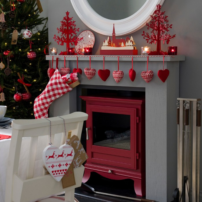 christmas fireplace, decorated with white and red, stuffed heart ornaments, hanging from a red and white rope, small candles and red christmas tree figurines