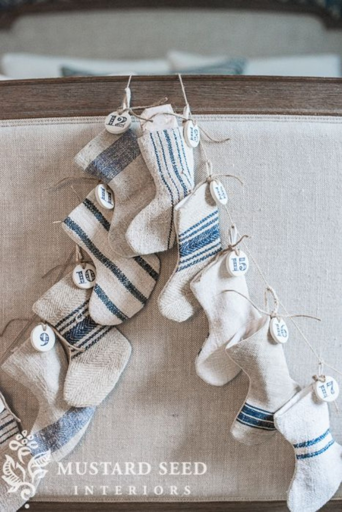 burlap small decorative stockings, in pale beige, with inky blue stripes, hanging on a piece of rope, each stocking has a small, round white tag, with a number, from 1 to 24