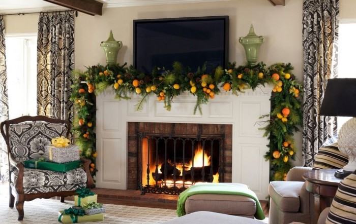 lemons and oranges, decorating a green garland, made from assorted leaves and branches, draped over a white fireplace, fireplace decor, in a clasically furnished room