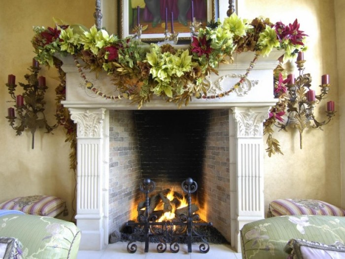 different kinds of faux leaves, in various shades of green, and in dark red, on a christmas garland, draped over a vintage style hearth, fireplace mantel decor, black metal grate