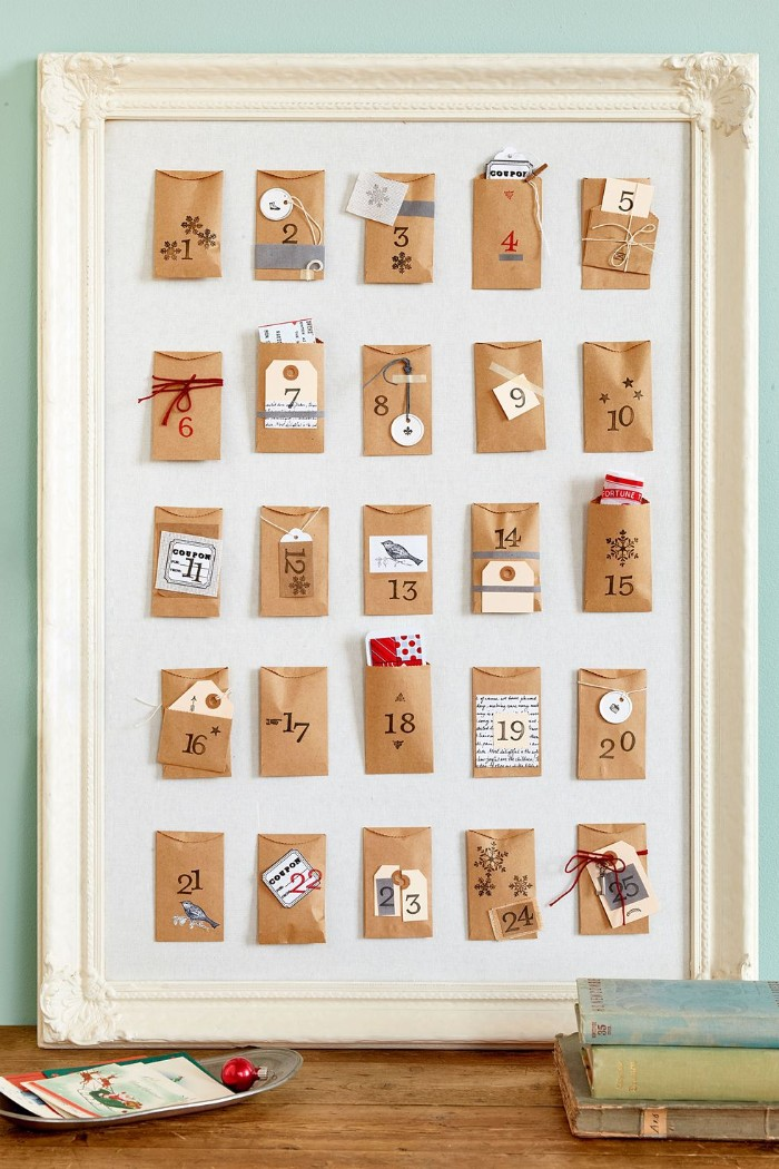 framed white board, containing 25 small, numbered beige envelopes, decorated with stickers, colorful paper and yarn, advent calendar ideas, a creative diy