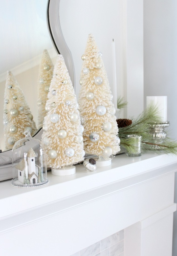 what to put on your christmas fireplace, two cream christmas tree figurines, adorned with white faux pearls, near a small church decoration, under a glass dome