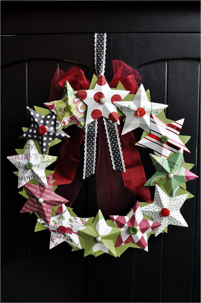 stars made from colorful patterned paper, stuck onto a wreath, decorated with pins and buttons, a sheer red bow, and a black and white ribbon, christmas wreath images, hanging on a black door