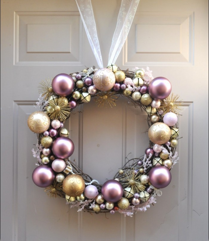 rose gold pearlescent christmas baubles, silver and gold ornaments, stuck together to form a christmas wreath, with a sheer ribbon handle