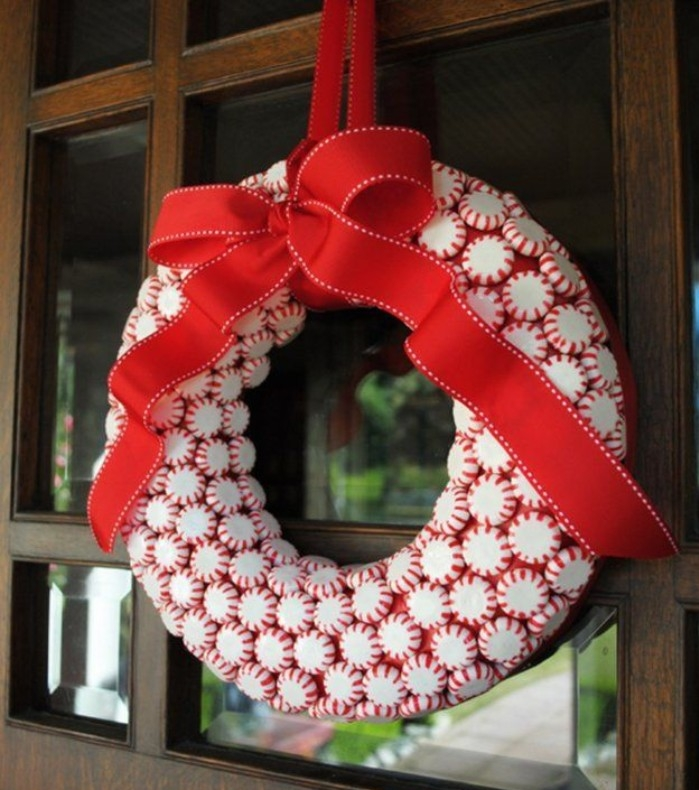 multiple peppermint candies, white with red stripes, stuck together to form a christmas wreath, decorated with a large, red ribbon tied in a bow
