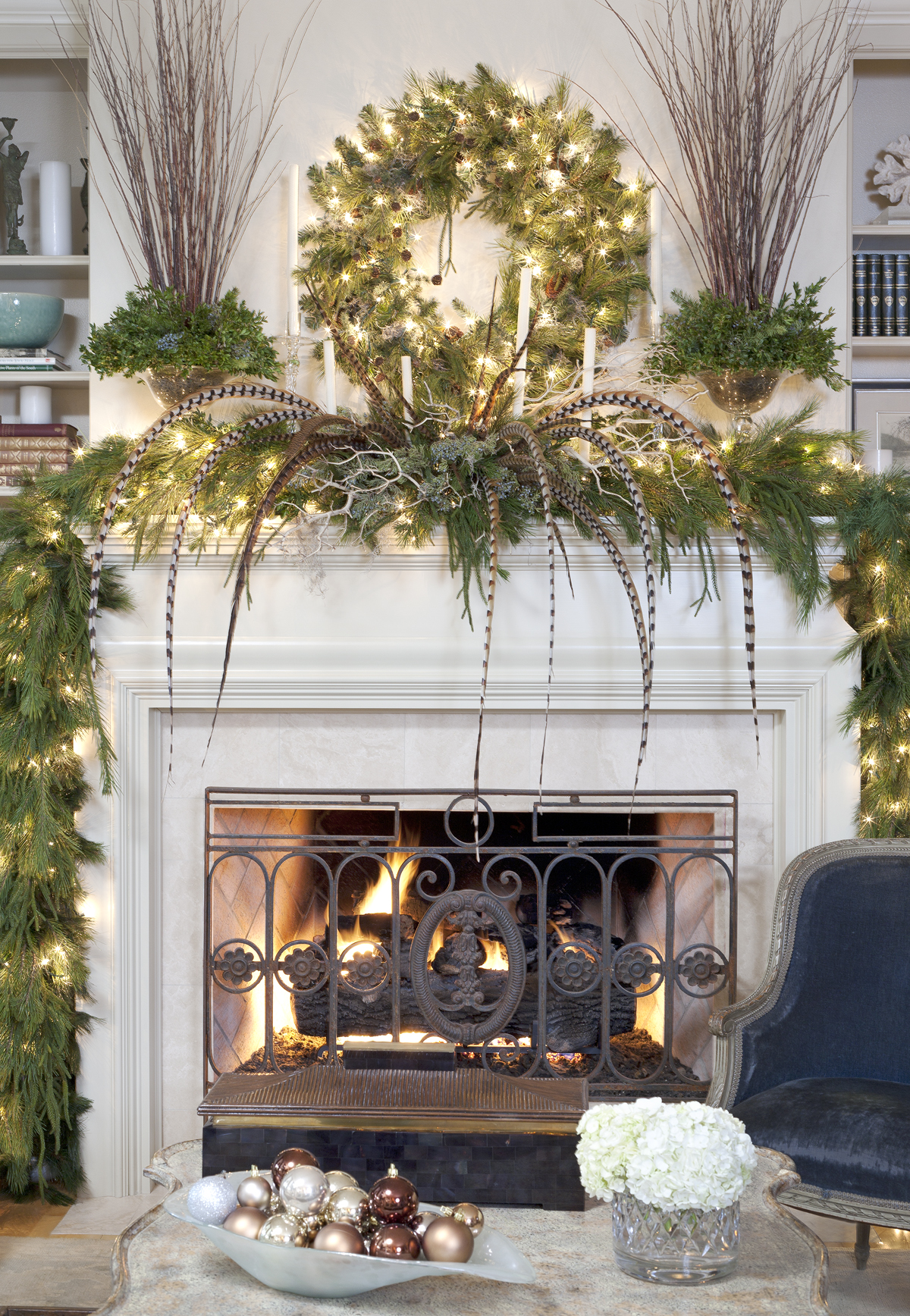 christmas mantel ideas, white lit fireplace, decorated with green pine garlands, a classic pine wreath, pheasant feathers and glowing string lights