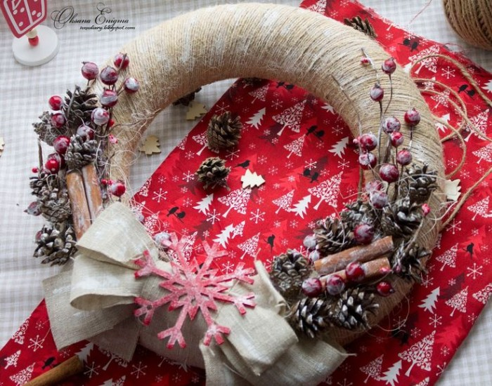 holiday wreaths, close up of a wreath, wrapped in beige string, and decorated with pinecones, red faux berries, cinammon sticks and a pale beige bow, with a large red snowflake ornament, all dusted in faux snow