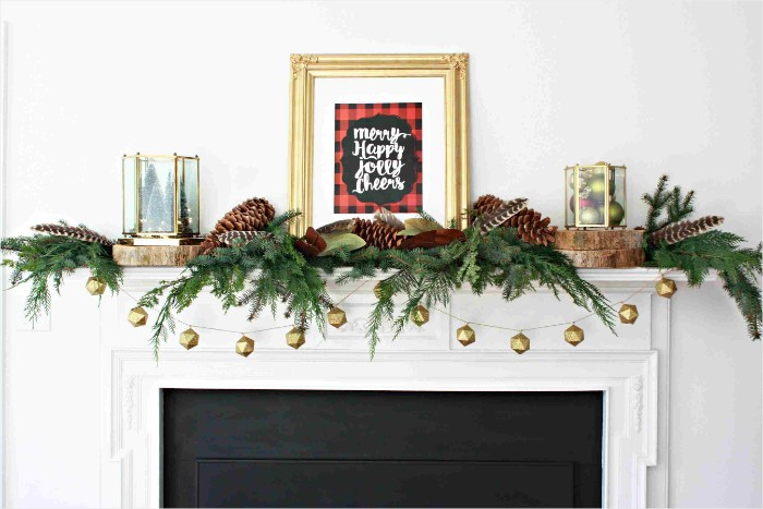 minimalistic christmas fireplace decoration, fir branches and pine cones, small garland with gold ornaments