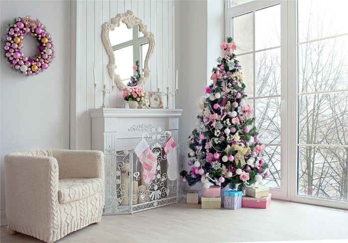 holiday images, bright room with large windows, white walls and a pale floor, containing a white fireplace, and a christmas tree, both decorated in gentle pink tones