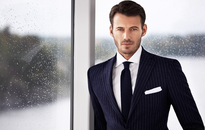 navy blue suit, with pinstripe pattern, worn by a brunette man, with stubble on the lower part of his face, cocktail attire for men, window with rain drops in the background