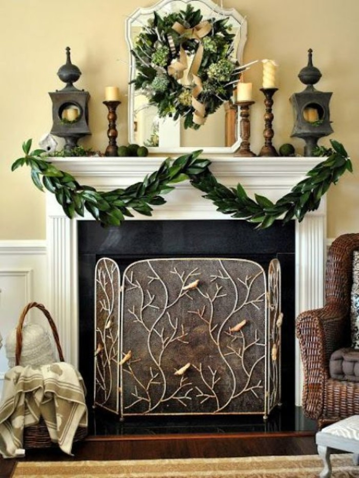 ornate fireplace grate, with branches and birds motif, placed in front of a black and white fireplace, decorated with a garland, made from green leaves