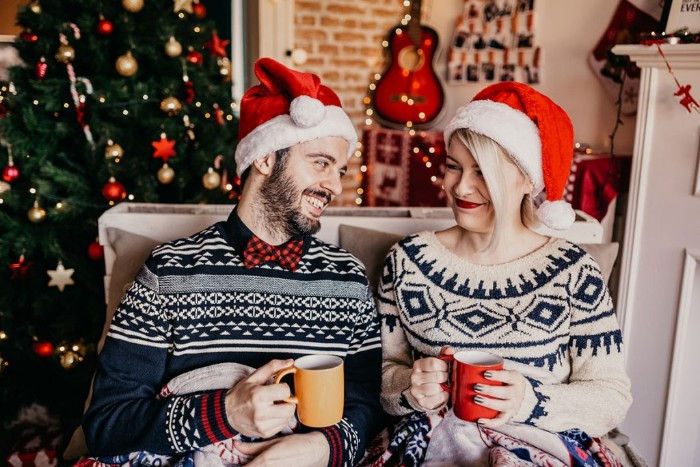 ugly christmas sweater ideas, couple wearing patterned winter jumpers, and santa hats, smiling while holding mugs