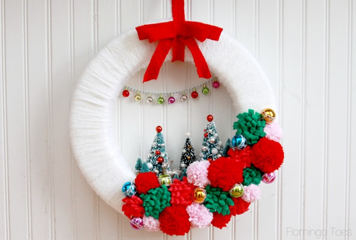 white yarn wrapped around a broad hoop, decorated with red, green and pale pink pompoms, three christmas tree figurines, miniature baubles on a silver chain, and a red bow, diy christmas wreath