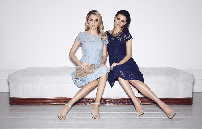 two women sitting on an off-white couch, wearing similar lace dresses, one in pale blue, and the other one in navy, cocktail attire