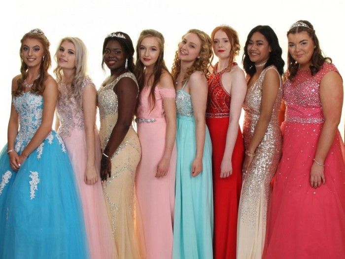 eight young girls, dressed in prom dresses, in different styles and colors, pale blue and powder pink, cream and gold, turquoise and coral pink, featuring embroidery and sequins