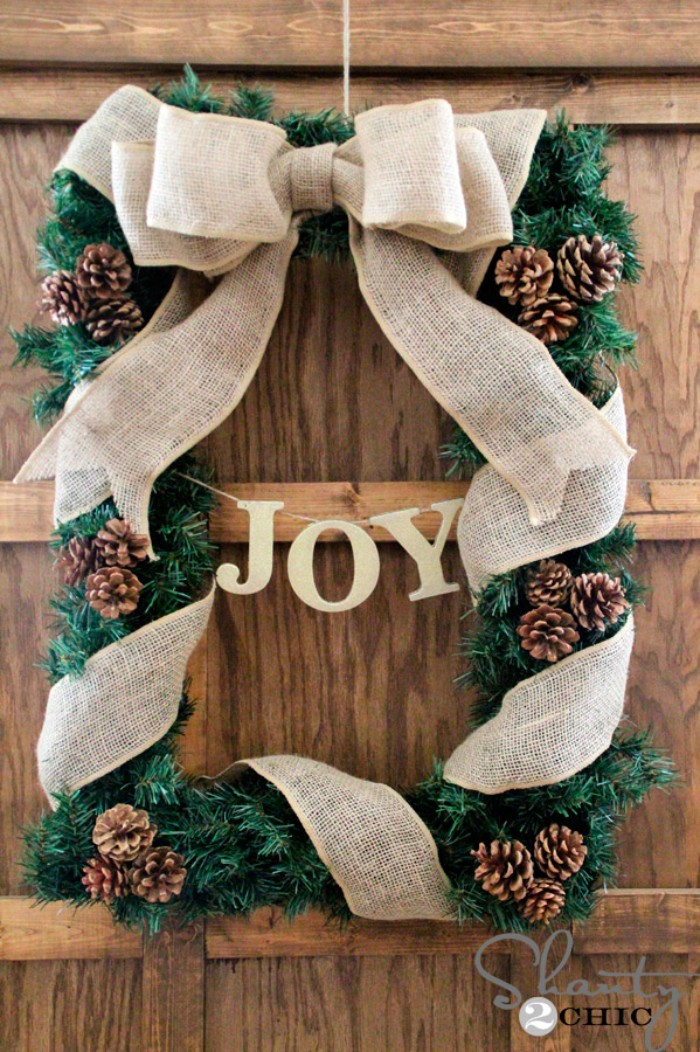 unusual rectangular wreath, made from faux pine branches, decorated with small pinecones, and wrapped in a burlap ribbon, tied into a bow at the top